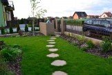 Ścieżka w trawniku z płyt imitujących kamień.